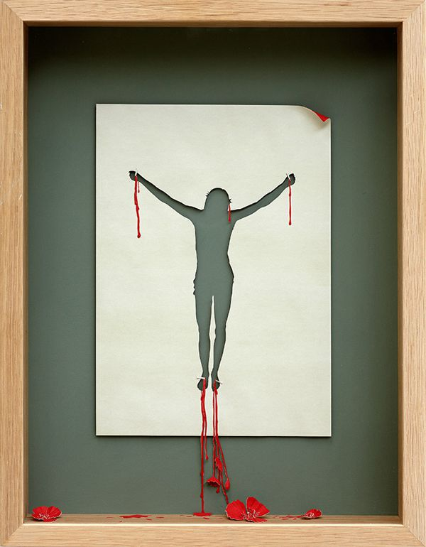 papercraft sculpture of an abstract jesus on the cross with blood by Peter Callesen