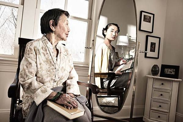 older asian woman sitting and looking in mirror and seeing her younger self as a young woman