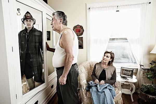 photograph of older man with wife looking in mirror and seeing reflection of his younger self as a fireman