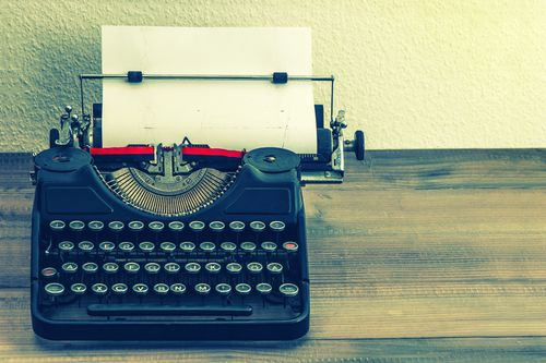 retro typewriter with white paper page on wooden table. vintage style toned picture
