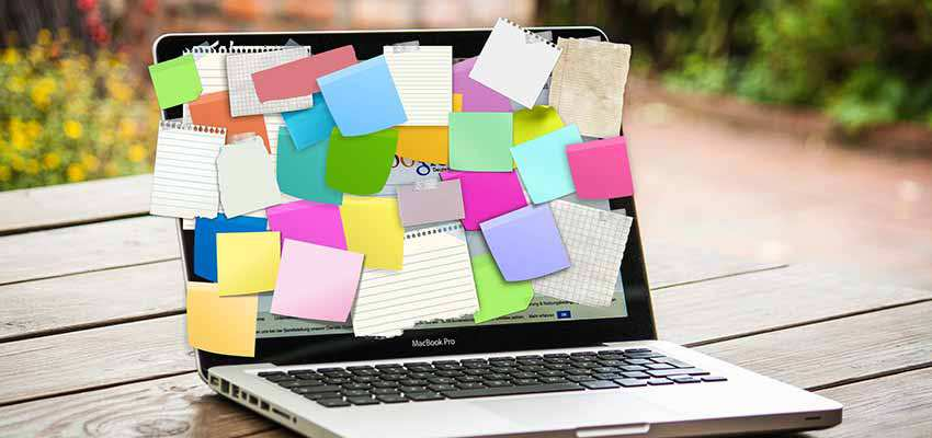 A laptop full of sticky note reminders.