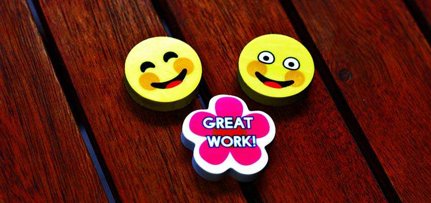 "Erasers with smiley faces and a badge that says ""Great Work"""