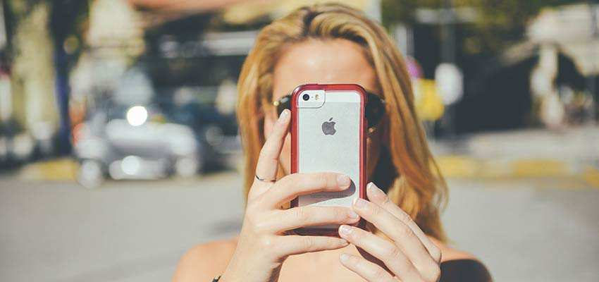 Woman looking at her iPhone screen.
