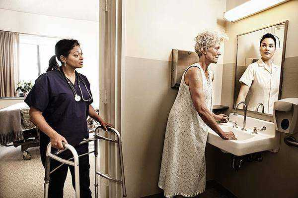 older lady in hospital looking in mirror and seeing reflection of her younger self as a young nurse