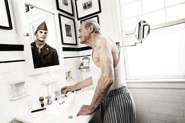smiling old man in bathroom looking in mirror and seeing reflection of his younger self as a soldier