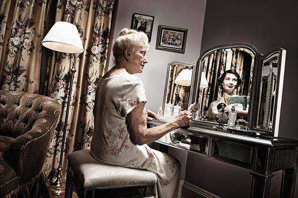 old glamourous woman looking in mirror and seeing reflection of her younger self as a beautiful woman