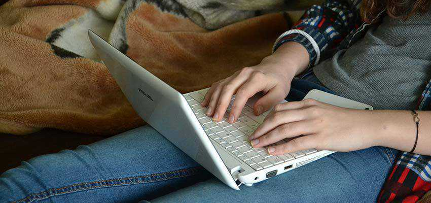 Woman typing on a laptop computer.