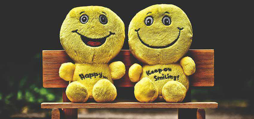 Two emoji stuffed dolls on a bench.