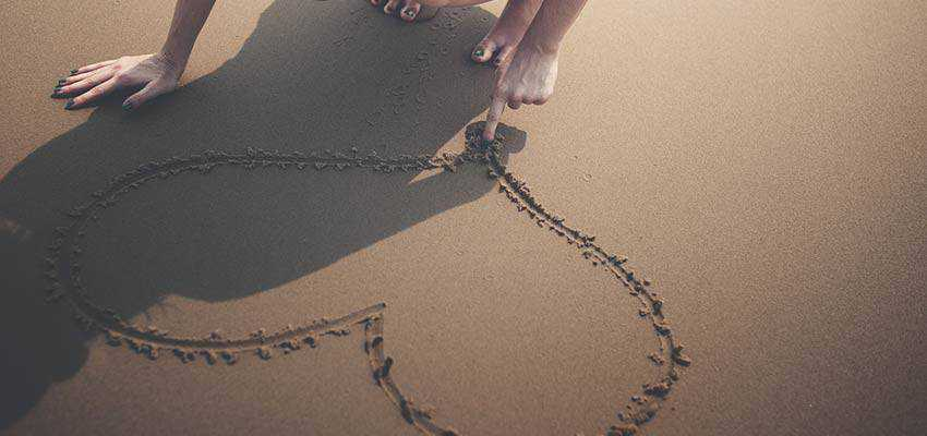 A woman drawing a heart in sand.