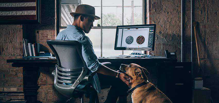 Man sitting at a computer, petting a dog.