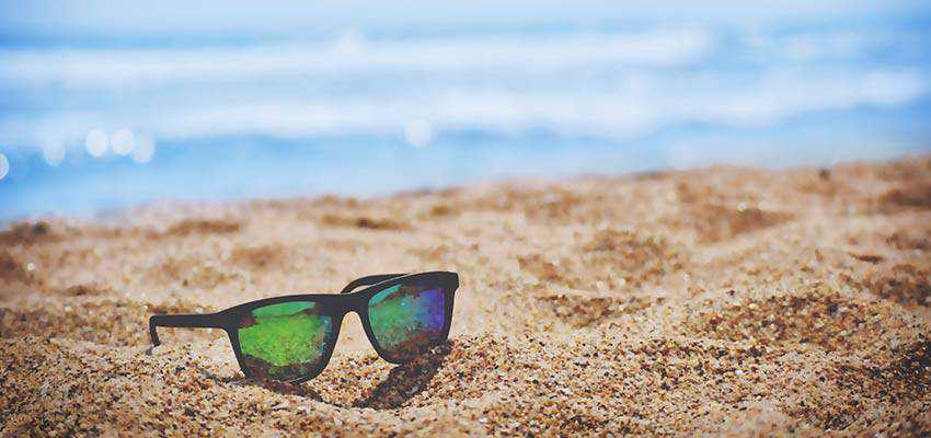 A pair of sunglasses sitting on a sandy beach.
