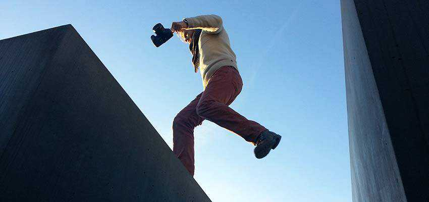 Man jumping between building roofs.