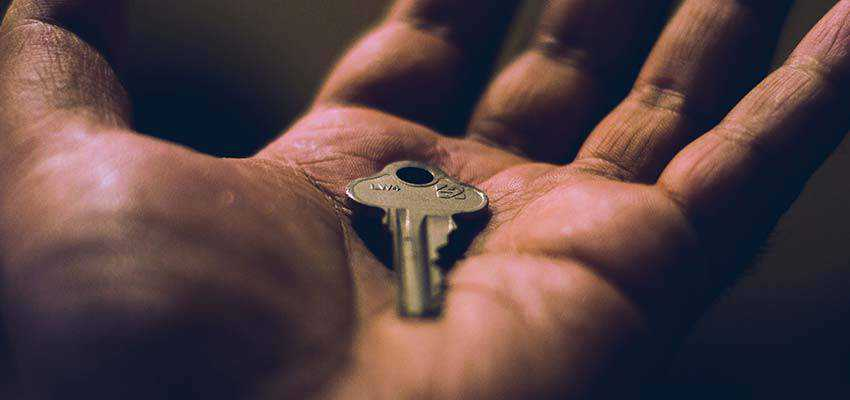 Man holding a key in hand.