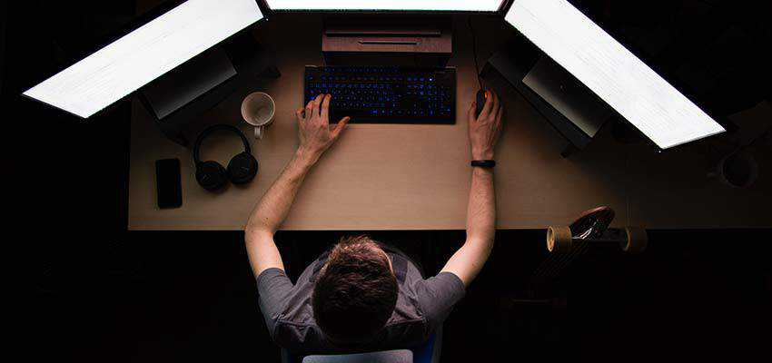 Man in front of three computer monitors.