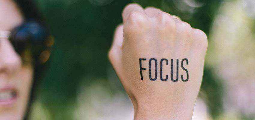 "A woman with the word ""Focus"" written on the back of her hand."