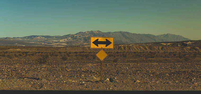 Directional sign on a desolate road.