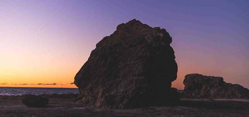 A large rock on a beach.