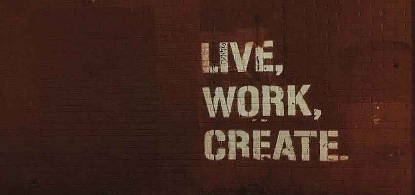 "A wall with the words ""Live, Work, Create"" painted on it."