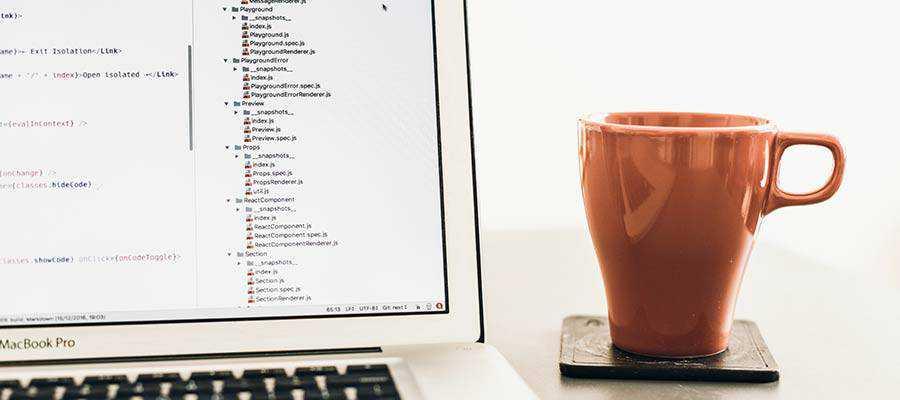 A mug sitting next to a computer.