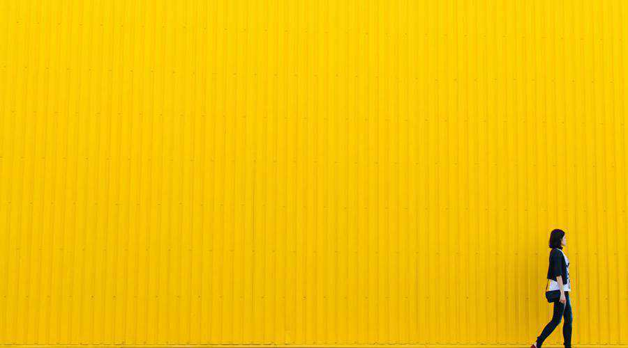 Woman Walking Past Yellow Wall minimal minimalistic desktop wallpaper hd 4k high-resolution