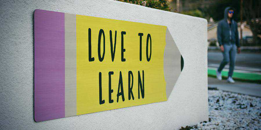 love to learn sign yellow wall