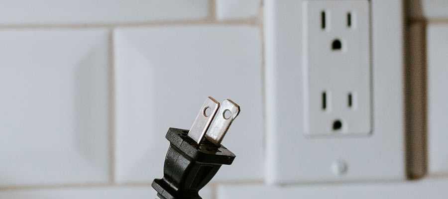 A electrial plug near an outlet.