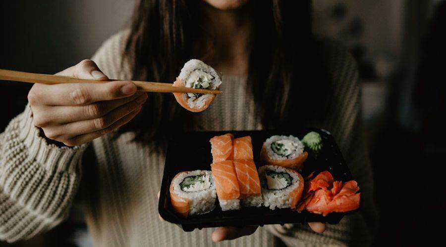 woman eating sushi simple plate