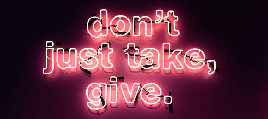 "A neon sign that reads: ""Don't just take, give""."