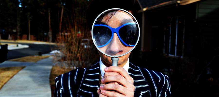 A person looks through a magnifying glass.
