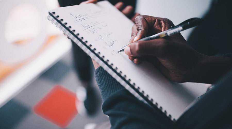 creative designer taking notes notepad pen