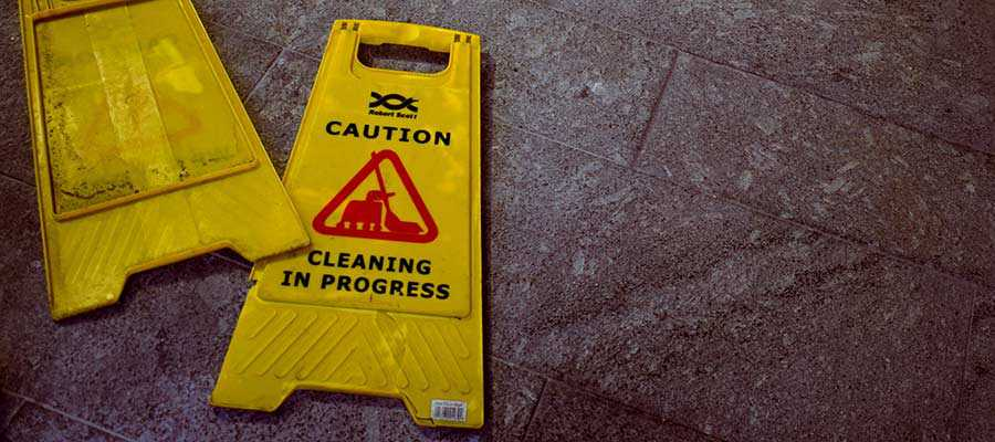 Cleaning signs lay on a floor.
